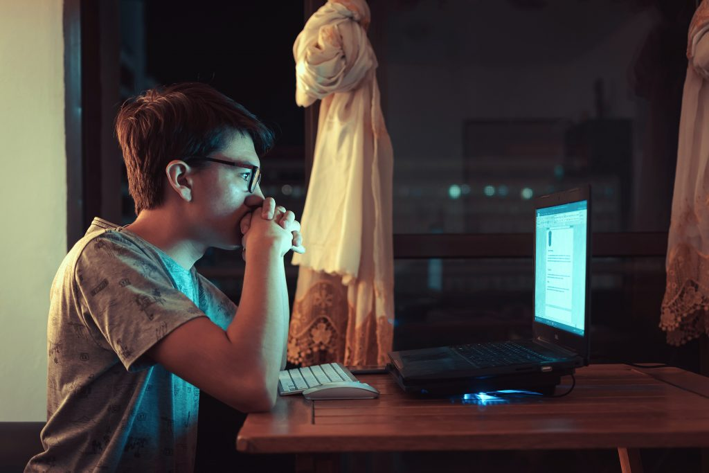 Person reading on a computer at night