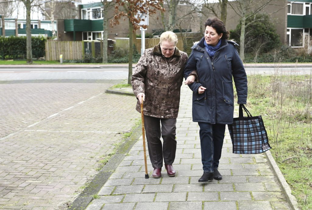 A carer assisting an elderly woman with walking