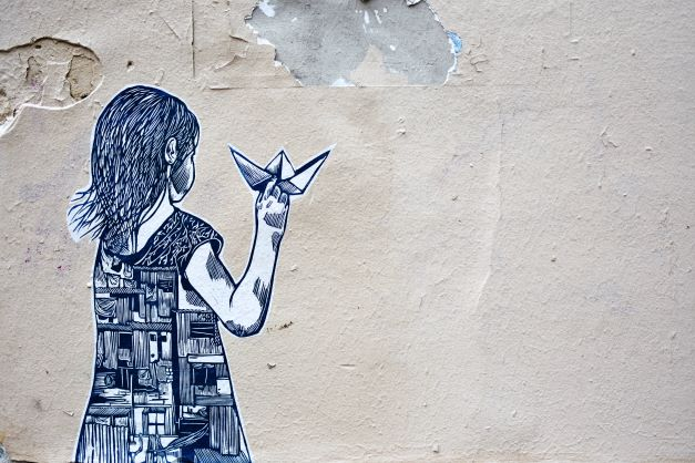 Graffiti of back of a girl with a paper plane