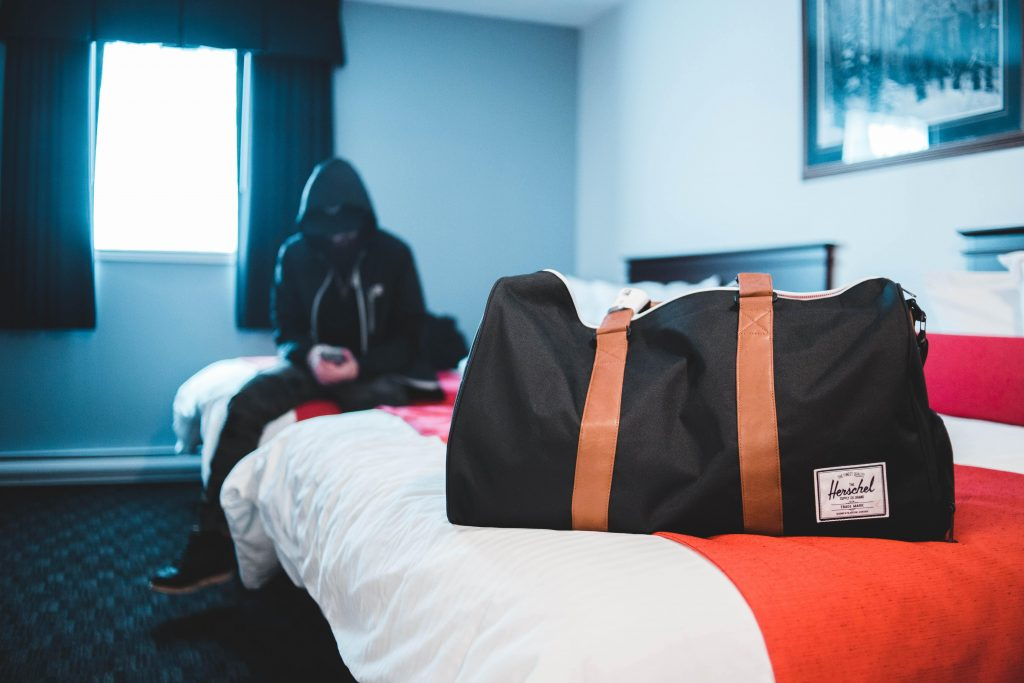 Person sat on the bed with bag packed